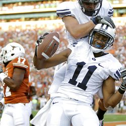 Wide receiver Ross Apo #11 of the BYU Cougars celebrates a second quarter touchdown pass against the Texas Longhorns with teammate J. D. Falslev #12 on September 10, 2011 at Darrell K. Royal-Texas Memorial Stadium in Austin, Texas.  (Photo by Erich Schlegel/Getty Images)