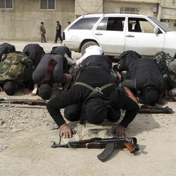 In this Sunday, April 1, 2012 photo, Free Syrian Army fighters perform the noon prayer in a neighborhood of Damascus, Syria.