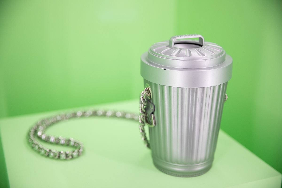 A purse in the shape of a little metal trash can.
