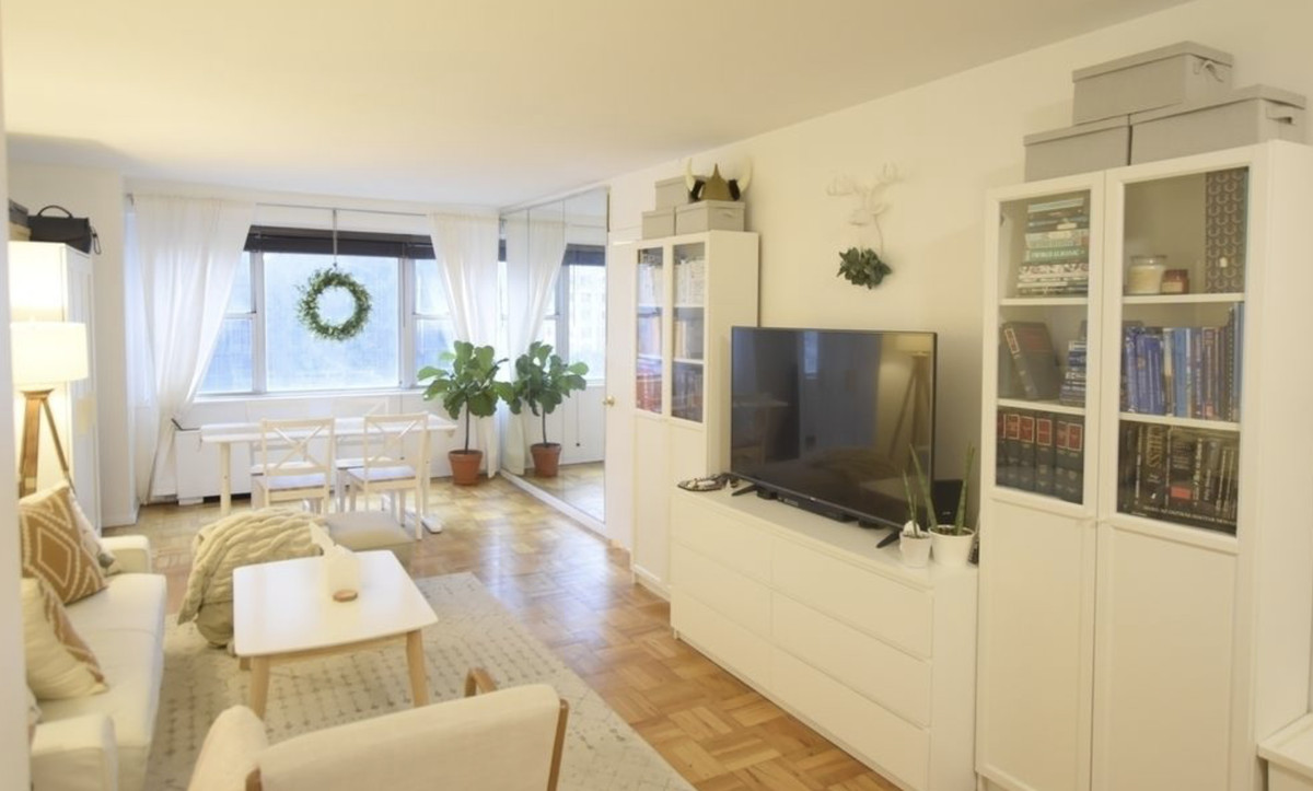 A living area with hardwood floors, white furniture, a TV on a stand, and a large window.