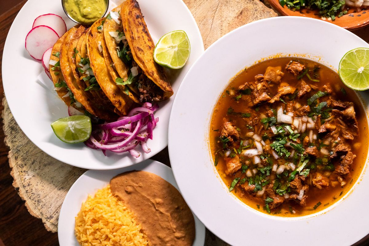 White plates of brick red birria stew and and crispy fried tacos surrounded by sliced limes, red onions, and slices of radish.
