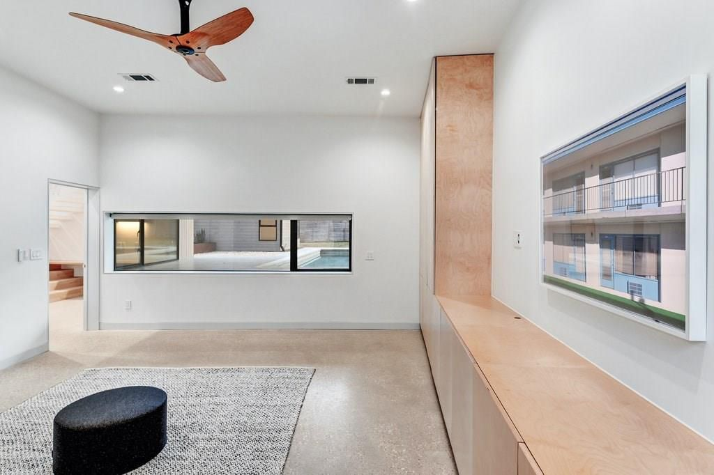 Interior photo of a room, maybe a bedroom or study, with a polished concrete floor and a L-shaped cabinet running up one wall and horizontally down the adjacent one. There's a three-paned horizontal window facing a pool outside. There's a rug under a circular ottoman in the center of the room.