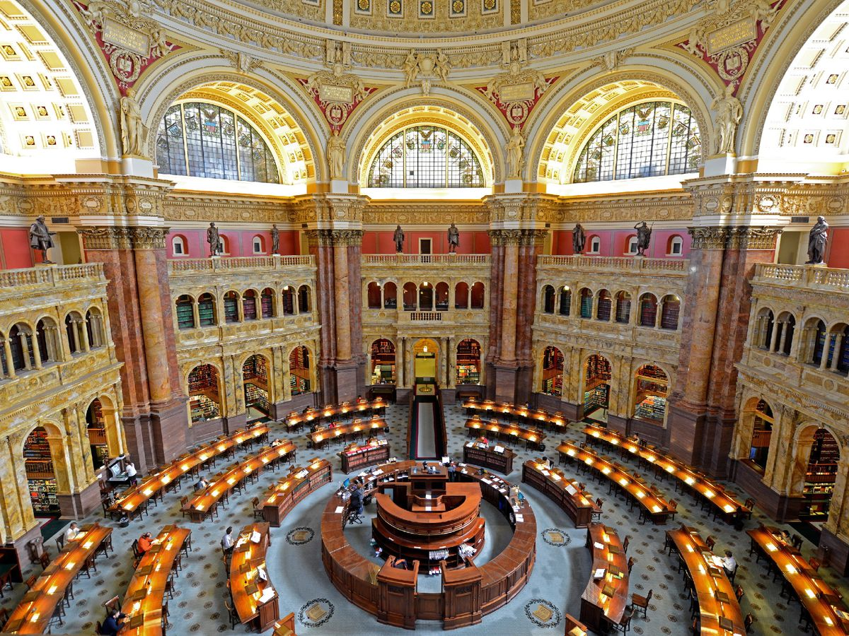 The huge reading room of a neoclassical library, filled with desks arranged in a circle.