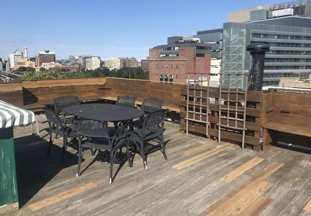 A roof deck with a table and chairs, and city buildings in the near distance.