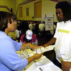 Sylvia Godfrey from Hill Air Force Base hands Phillip Johnson an employment application Thursday during the job fair held at Camp Williams. More than 100 companies reportedly wanted to take part in the job fair.