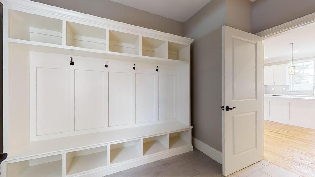 A walk-in closet with hooks and cabinetry.