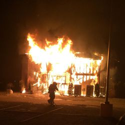 This photo provided by Bellevue, Wash., Fire Department, a fire burns at the Islamic Center of the Eastside in Bellevue, Wash., on Saturday, Jan. 14, 2017.  Police say a man is in custody after a suspicious fire severely damaged the mosque overnight.  Authorities say that as firefighters doused the flames, police found a 37-year-old man near the building and arrested him for investigation of arson. Police spokesman Seth Tyler says investigators believe the man is the sole suspect. The mosque was unoccupied at the time and no injuries were reported.