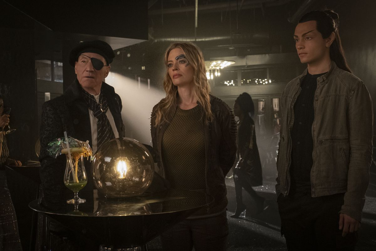 Star Trek: Picard series hero Picard, in costume in a beret and eyepatch, stands next to former Borg Seven of Nine, who has her hands cuffed behind her back. Picard's Romulan ninja ally Elnor, in a frumpy brown jacket, stands next to them looking like he isn't paying attention.