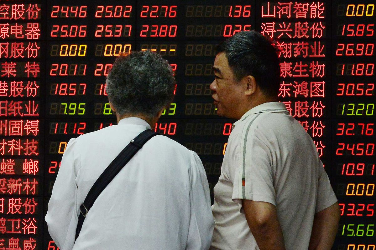 Investors talk in front of a board displaying share prices at a security firm in Shanghai on July 1, 2015.