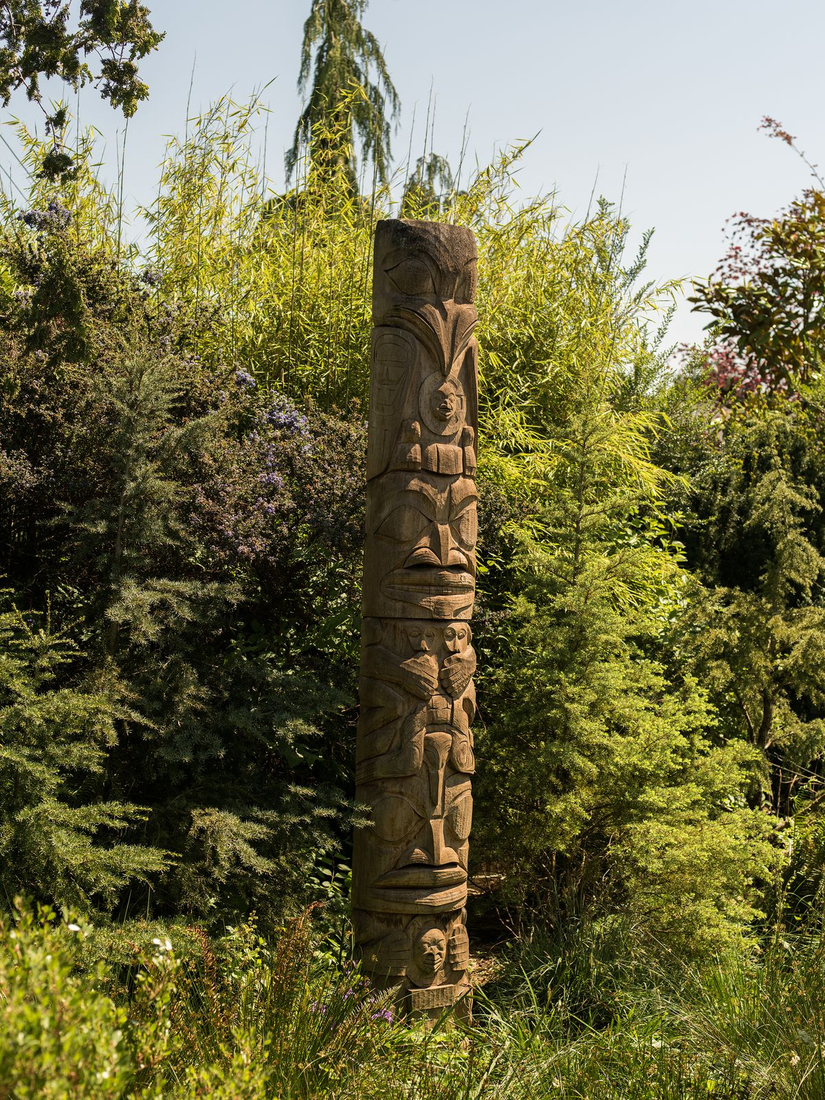 A wooden totem pole in a garden full of lush green trees and bushes.