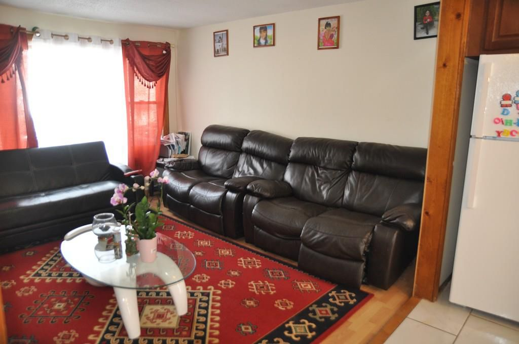 A close-up on the small living room, with a sectional couch and a rug.