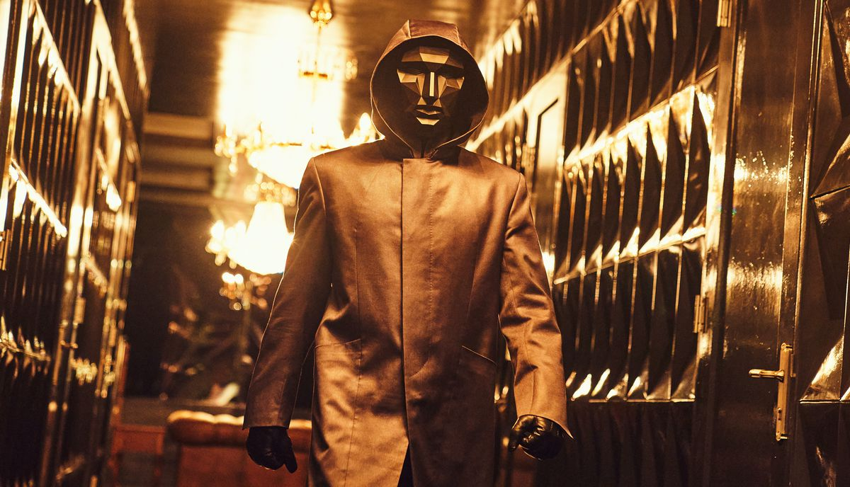 A masked figure in gold moves through a gold room in Netflix's Squid Game