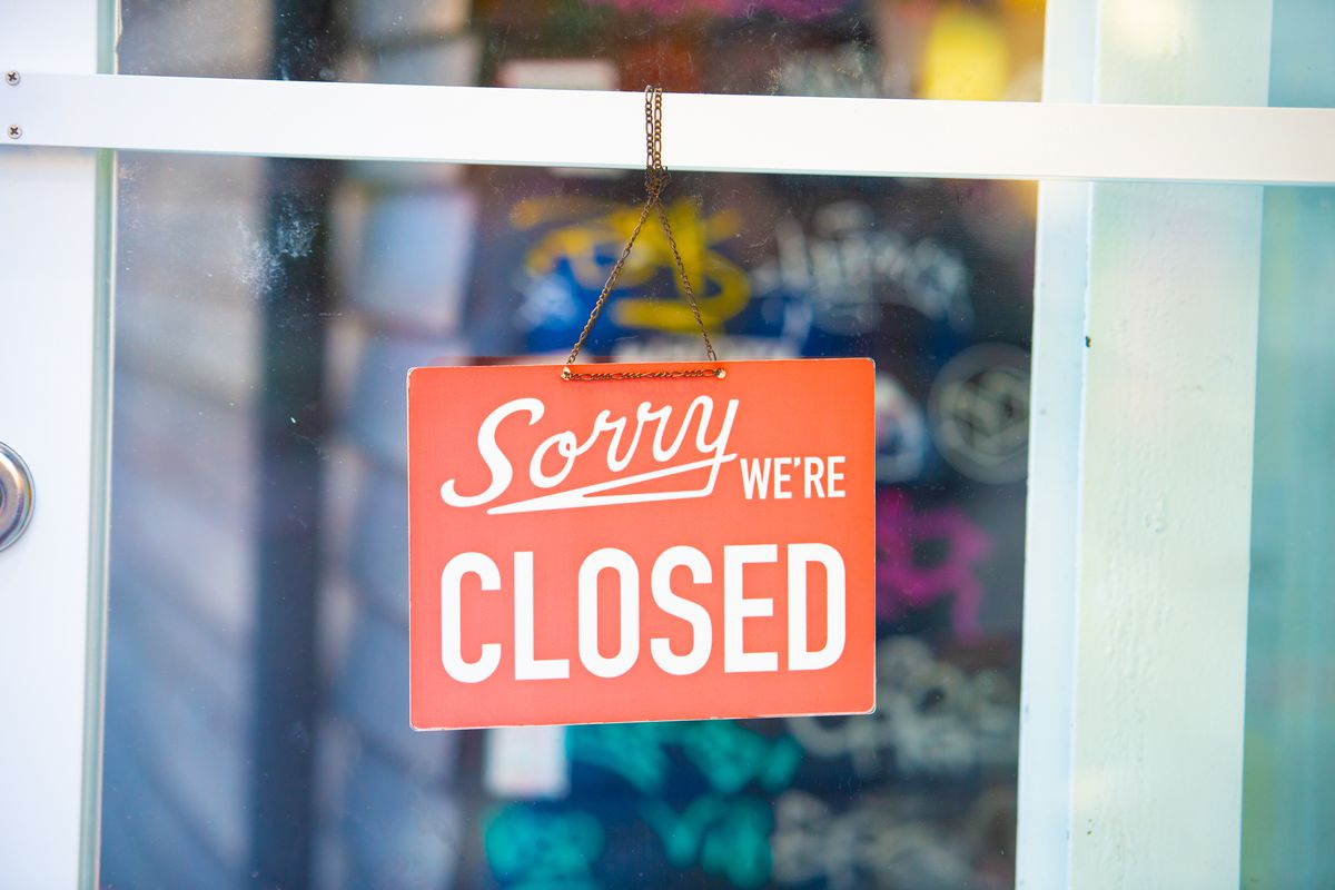 A sign posted in a restaurant window informing customers that the restaurant is closed.