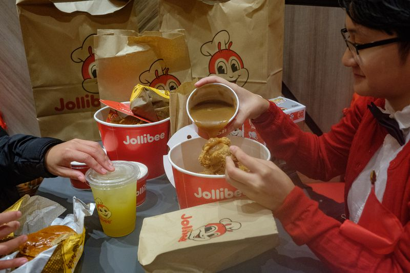 A Jollibee customer pours gravy on her Chickenjoy, a common Filipino use of the gravy.
