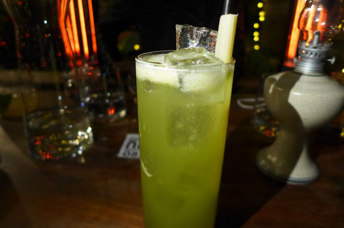 A tall glass filled with green liquid, ice, and a stick of sugar cane.