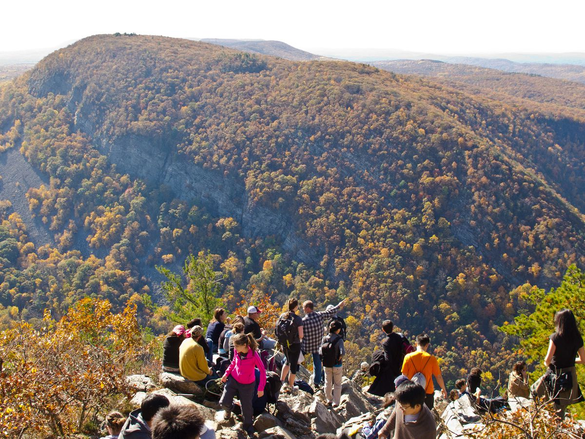 In the foreground are people standing at the edge of a cliff. In the distance is a mountain covered with trees which have multicolor leaves. It is autumn.