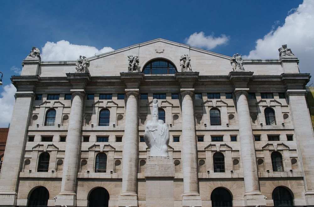 The exterior of the Italian Stock Exchange in Milan. The facade has columns and there is a statue in front of the building.