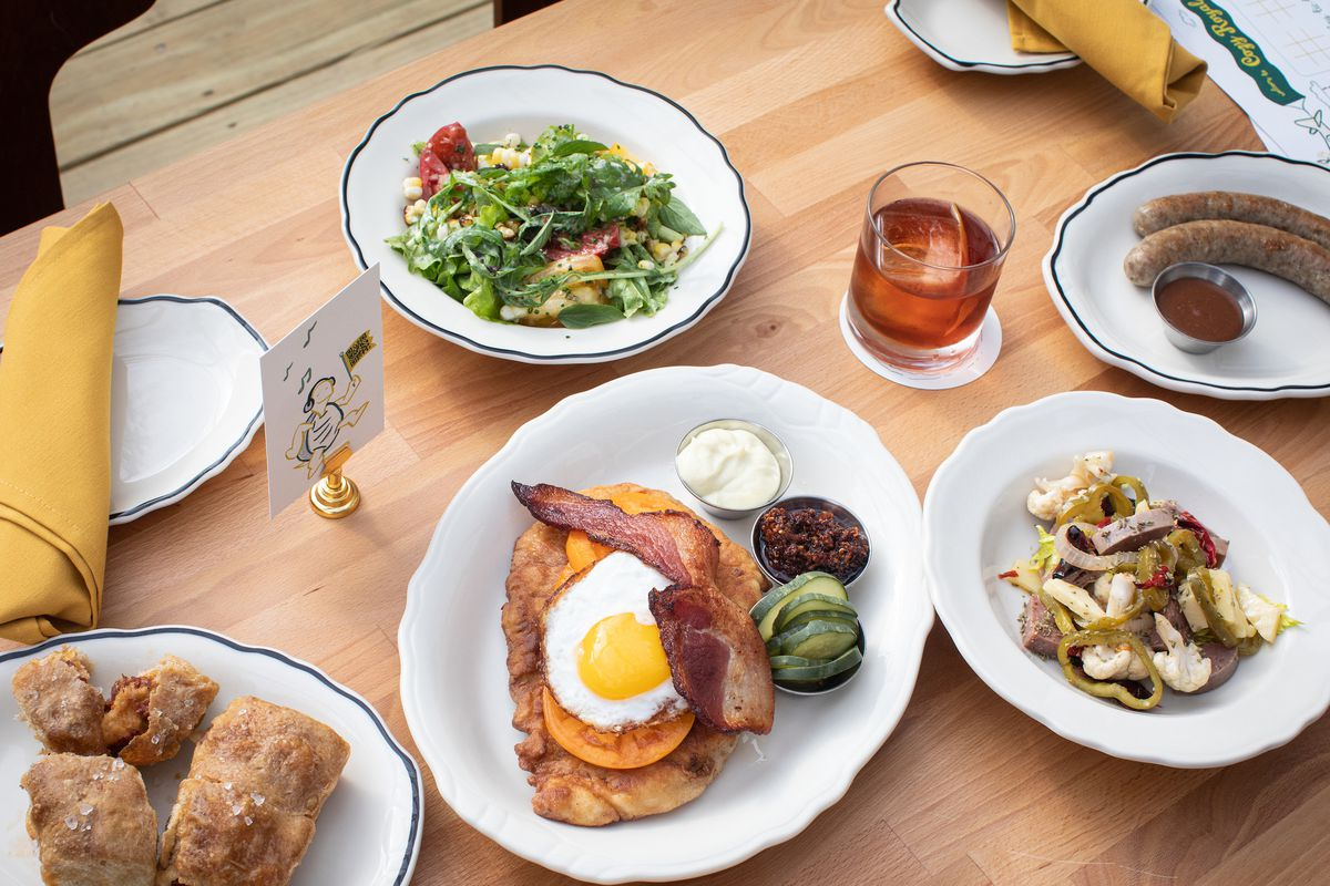 A spread of food including salad, pepperoni balls, and fried pork with an egg displayed in white porcelain dishes on top of a brown wooden table
