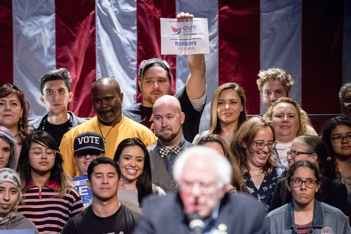 "A man holds up a ""medicare for all"" sign as Sen. Bernie Sanders, I-Vt., speaks at a rally for Senate candidate Rep. Jacky Rosen, D-Nev., and other Nevada Democrats at the Performing Arts Center in Las Vegas on Thursday, Oct. 25, 2018."