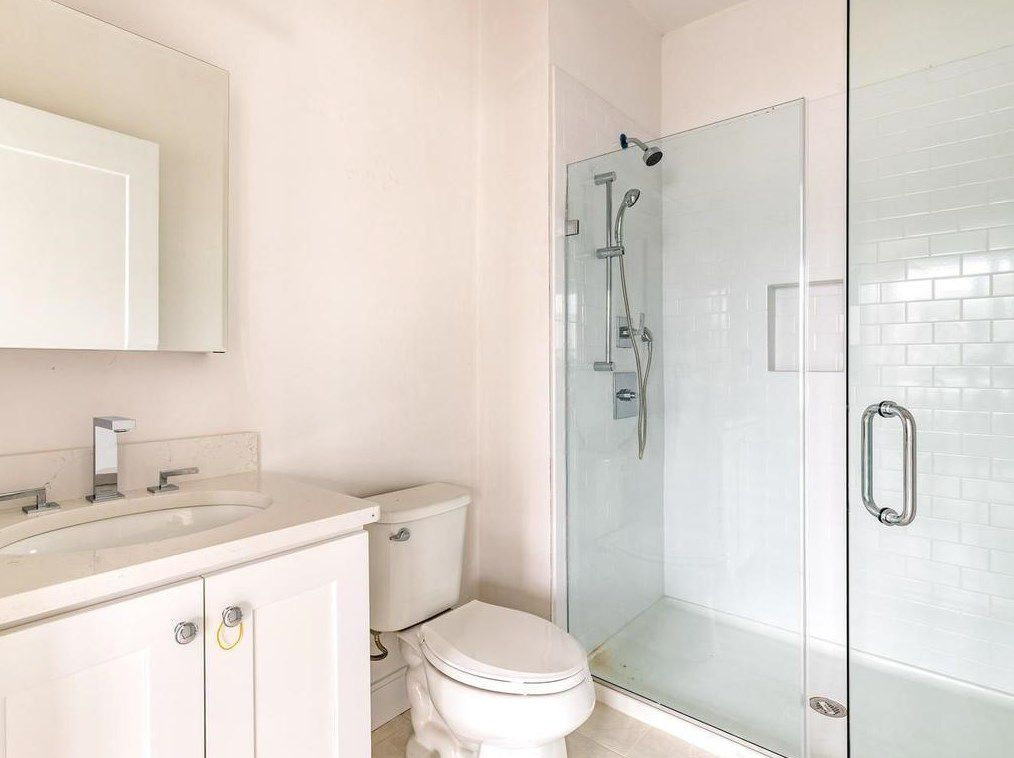 A bathroom with a toilet next to a glass-enclosed shower.