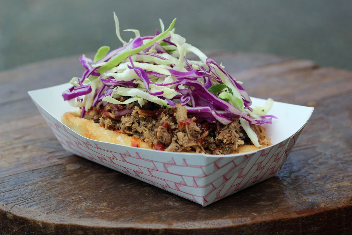A closeup view of a pile of Off the Rez Cafe's pulled pork fry bread taco inside a paper bowl, topped with coleslaw.