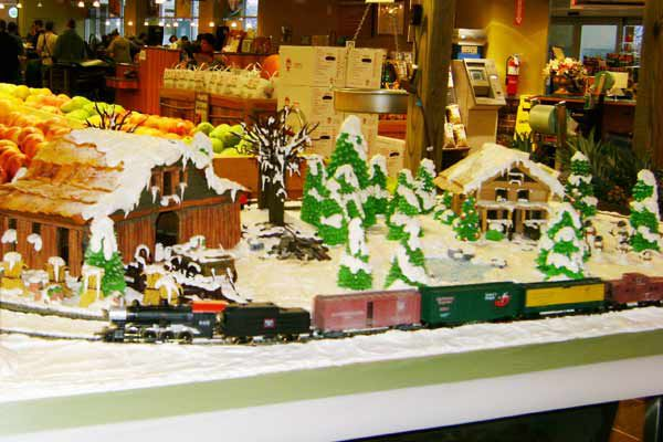 Gingerbread display in the bakery with a few houses, many Christmas trees, and a train track running through the town.
