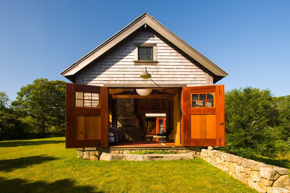 Shot of the side of a barn-style home with two large doors opening into it.