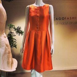 """<a href=""""http://laginadeau.com/"""">Lagi Nadeau</a> was inspired by the Desert Candle's """"bright orange color, unique texture, and shape."""" Made from an orange silk-wool fabric, the dress """"mimes the silhouette of the [flower]: slender on top and fuller at the"""