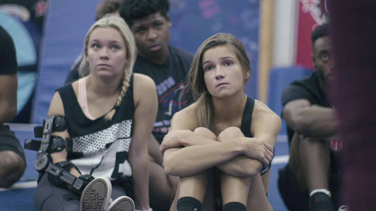 Two women cheerleaders sit on the mat in Cheer; one has a brace on her entire right arm