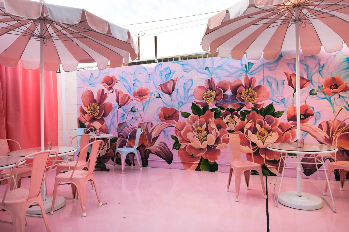 A floral mural and pink tables with pink umbrellas