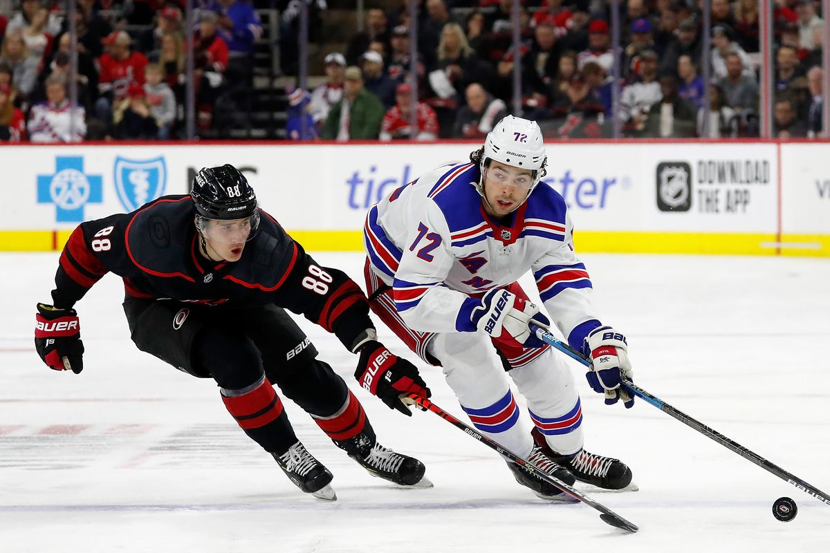 Filip Chytil of the New York Rangers controls the puck away from defending Martin Necas of the Carolina Hurricanes during an NHL game at PNC Arena on February 21, 2020 in Raleigh, North Carolina.