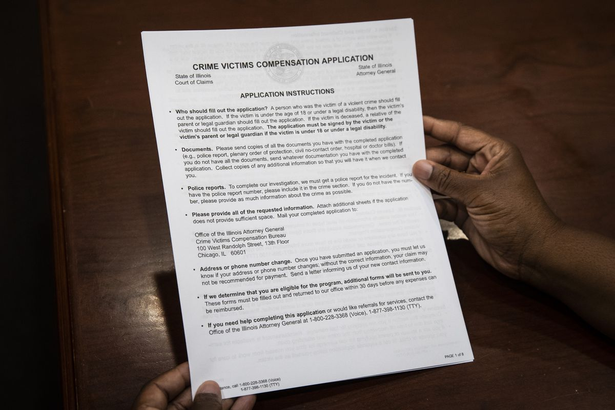 Austin funeral director Nhemya Ward holds a paper copy of the Crime Victims Compensation Application. It's five pages long, with more than 100 information fields