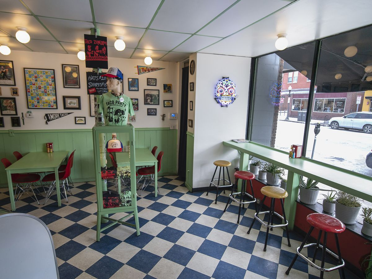 An interior of a casual restaurant features mint green and white walls, cherry red stools, and a green-and-white checkered floor.
