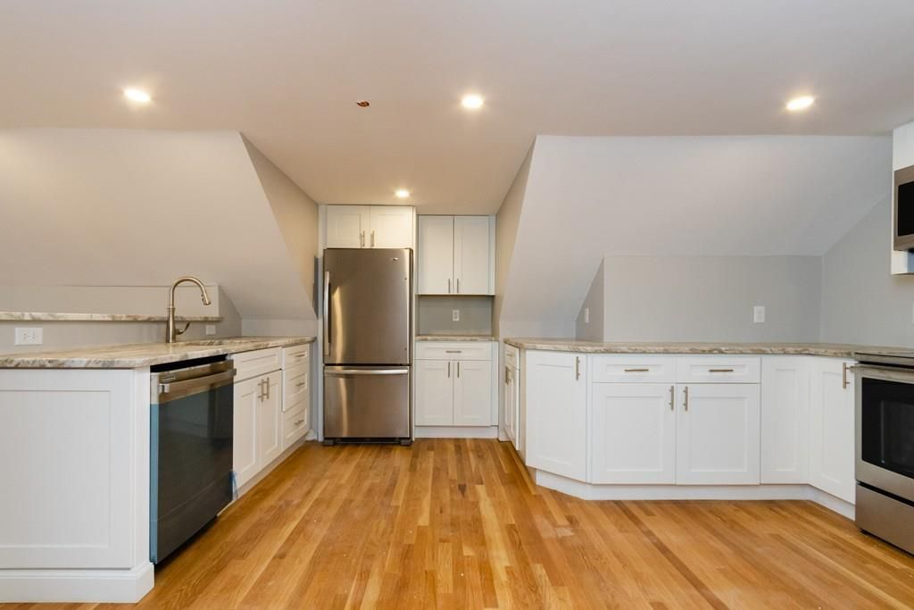 An open kitchen with a fridge at the center of the counter.