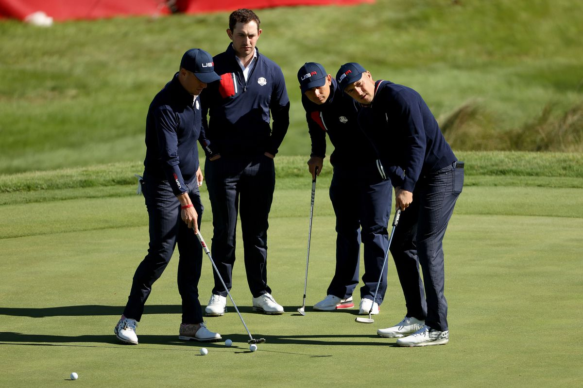 Justin Thomas of team United States, Patrick Cantlay of team United States, Jordan Spieth of team United States and caddie for Xander Schauffele of team United States, Austin Kaiser look on over the 18th green during a practice round prior to the 43rd Ryder Cup at Whistling Straits on September 22, 2021 in Kohler, Wisconsin.