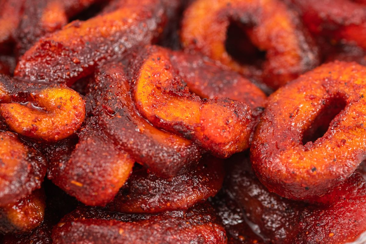 Peach ring candies coated in chili and chamoy syrup
