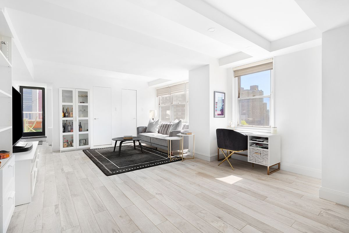 A living room area with hardwood floors, beamed ceilings, several windows, a black rug, and a light grey couch.