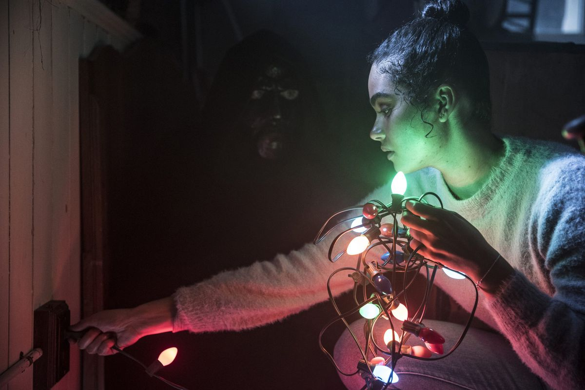 Jesse (O'Grady) tests a string of Christmas lights, illuminating a figure behind her.