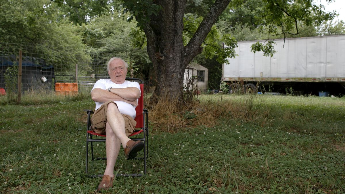 An older white man in a white T-shirt and cargo shorts sits in a backyard with his arms crossed.
