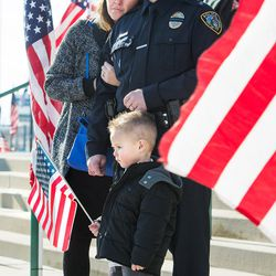 Draper officer Brian Larsen stands with his wife, Jamie, and son, Harrison, as the procession leaves following funeral services for Unified police officer Doug Barney at the Maverik Center in West Valley City on Monday, Jan. 25, 2016.