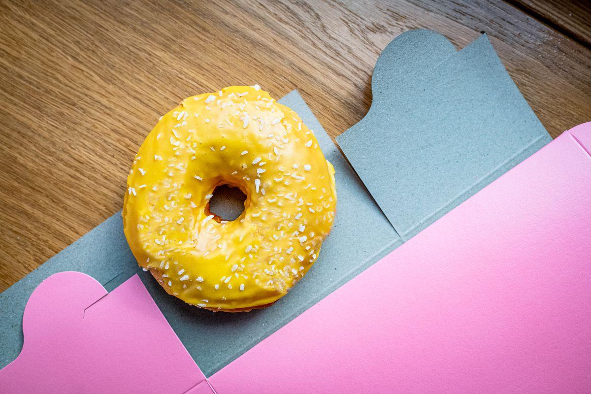 An overhead shot of a wide Donut Run doughnut with a bright yellow mango-coconut glaze sitting near a powder pink foldable box.