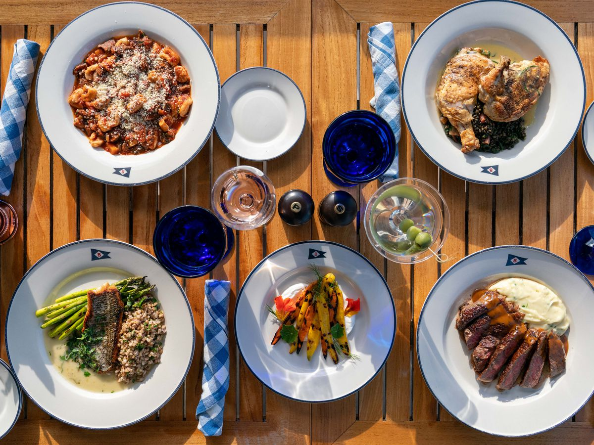 Four different dishes placed on a wooden table with some blue cutlery on the side