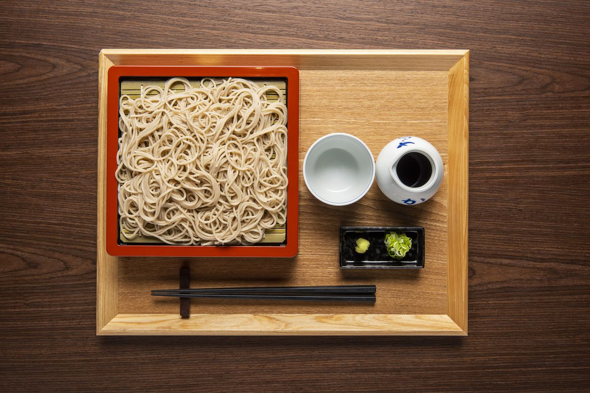 An overhead photograph of a plate of light-brown soba noodles, alongside a pair of chopsticks, wasabi, ginger, and a white cup