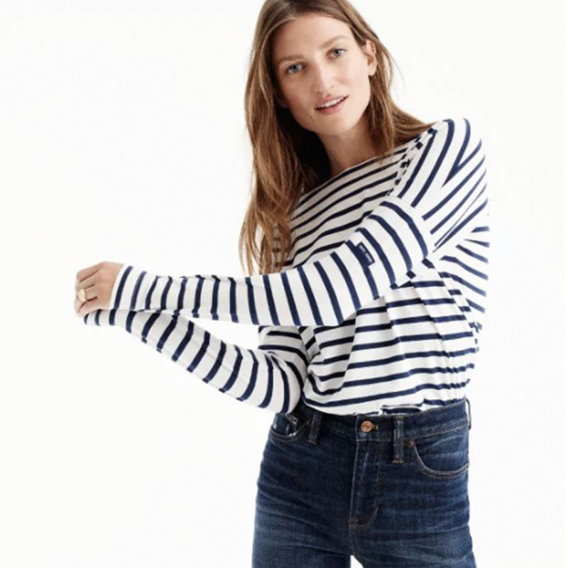 A model wearing a white tee with blue stripes.