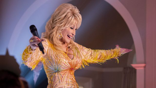 Dolly Parton in a fabulous gold dress, arms open, sending love to all her fans