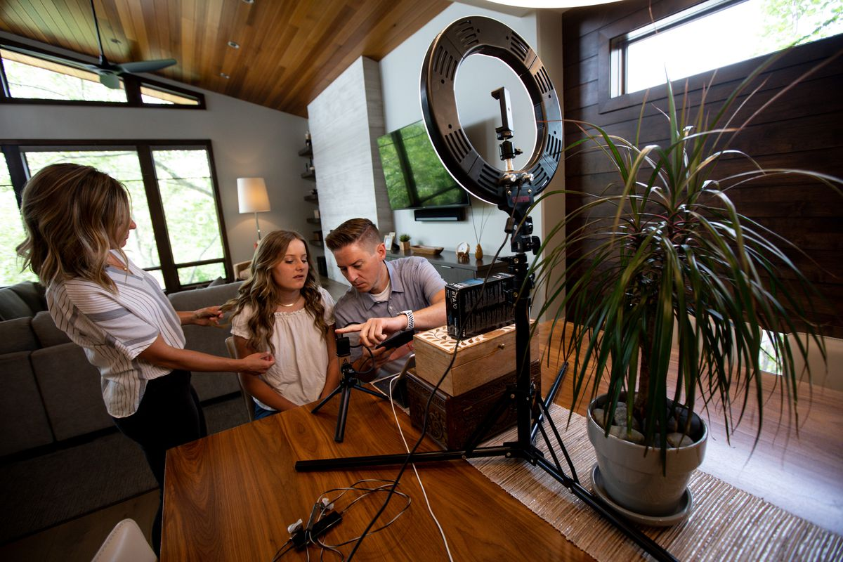 """Brooke Shaw fixes her daughter Savanna Shaw's hair while she and her father Mat Shaw prepare to record a cover of the song """"Shallow"""" in their family's home on Thursday, May 14, 2020. The father-daughter duets went viral on YouTube as they shared their passion for music amid the COVID-19 pandemic. """"The one thing more contagious than a virus is hope and so we're just doing our small part in the world to spread some hope,"""" Mat Shaw said."""