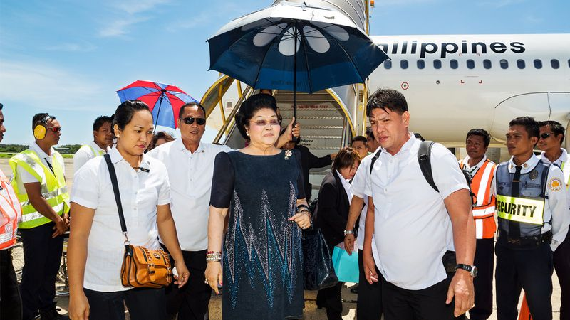Imelda Marcos standing outside a Philippines airliner and surrounded by staff, one of whom holds a parasol over her.