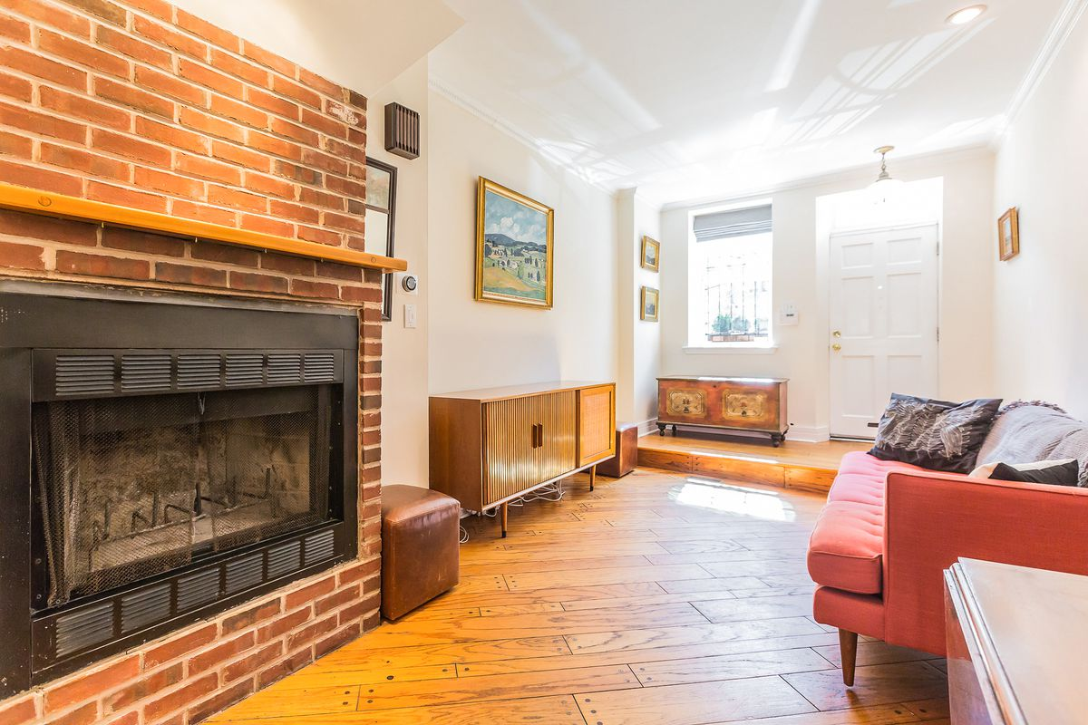 A warm and sunny living room with hardwood floors and a brick fireplace.