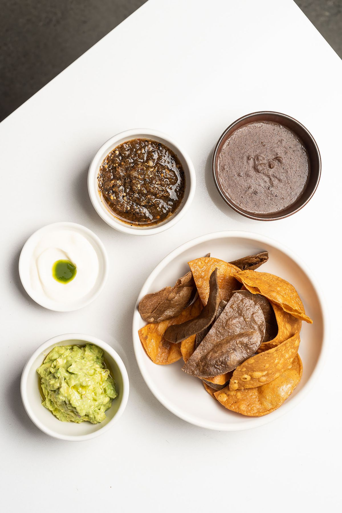 One large dish containing chips is surrounded by four smaller dishes, each holding a dip.