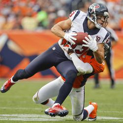 Houston Texans wide receiver Kevin Walter (83) brings down a pass as he is hit by Denver Broncos strong safety Chris Harris (25) in the fourth quarter of an NFL football game Sunday, Sept. 23, 2012, in Denver.